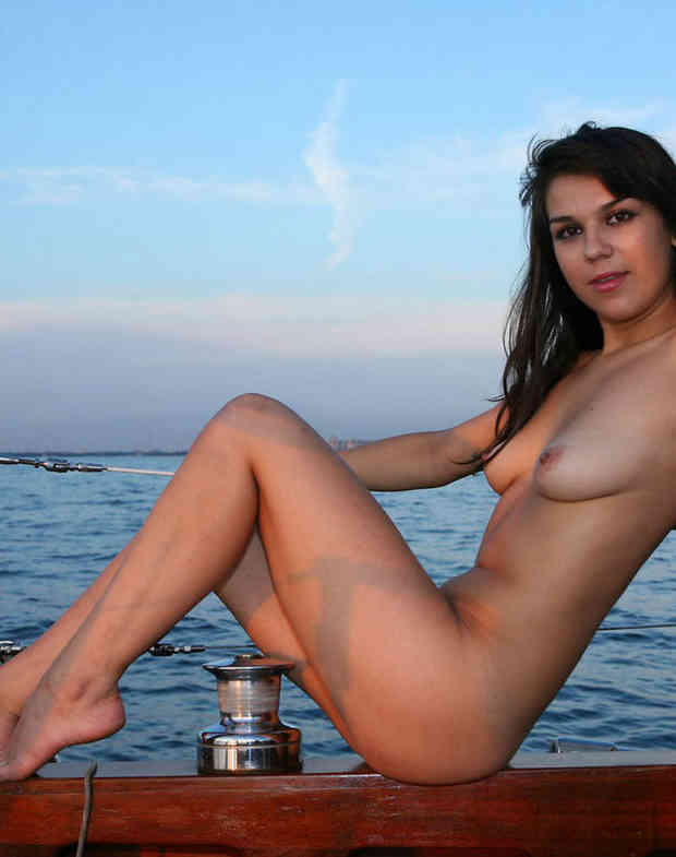 Lovely brunette posing absolutely naked on boat.