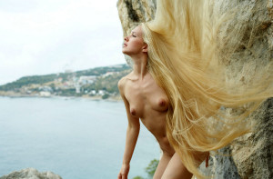 Naked-long-haired-blonde-posing-on-the-rocks-near-sea-1