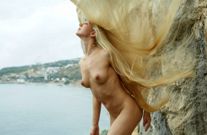 Naked-long-haired-blonde-posing-on-the-rocks-near-sea-13