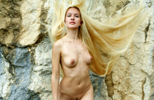 Naked-long-haired-blonde-posing-on-the-rocks-near-sea-14