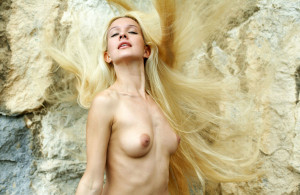 Naked-long-haired-blonde-posing-on-the-rocks-near-sea-15
