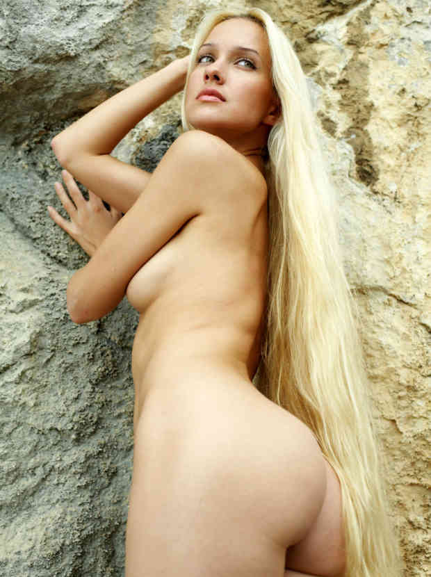 Naked long-haired blonde posing on the rocks near sea.