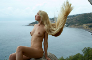Naked-long-haired-blonde-posing-on-the-rocks-near-sea-4