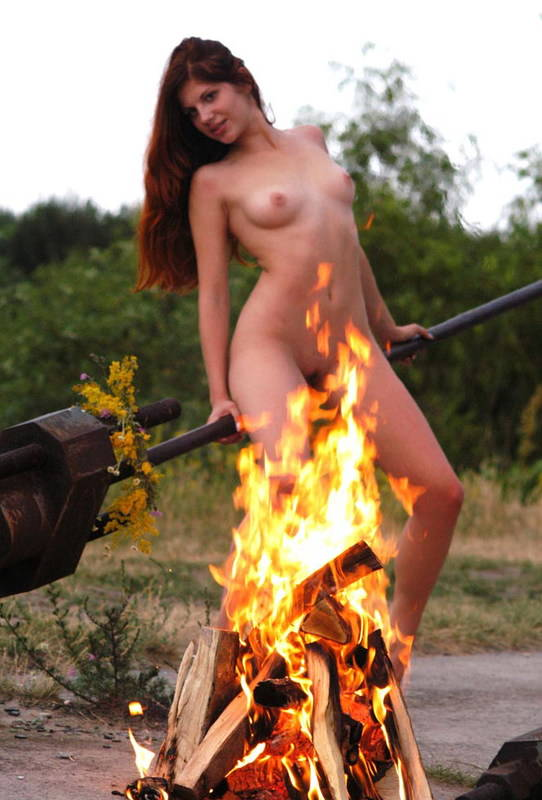 Naked redhead girl wears only floral wreath posing near bonfire.