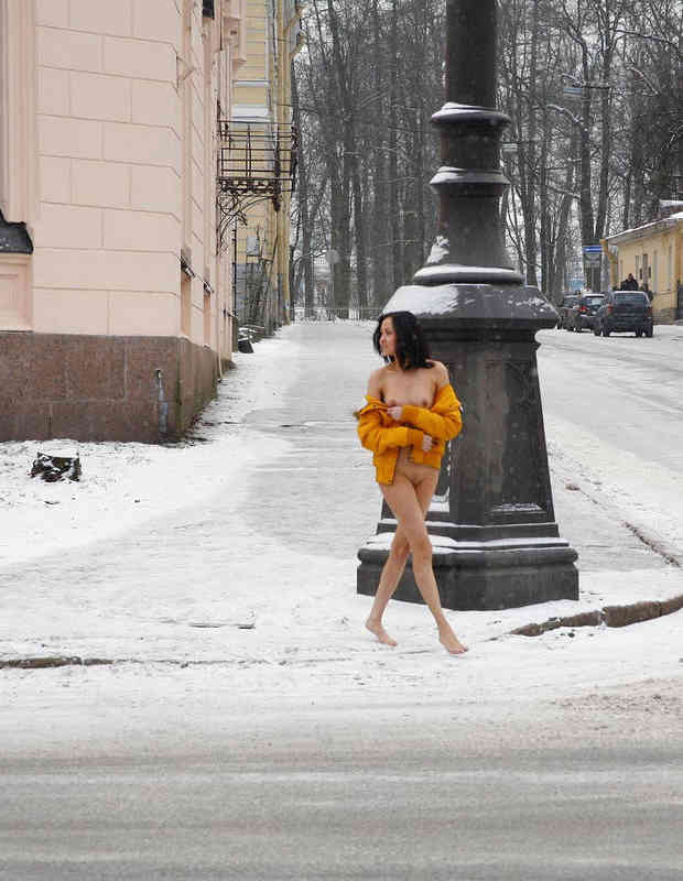 Russian brunette exhibitionist walks naked at public street at winter.