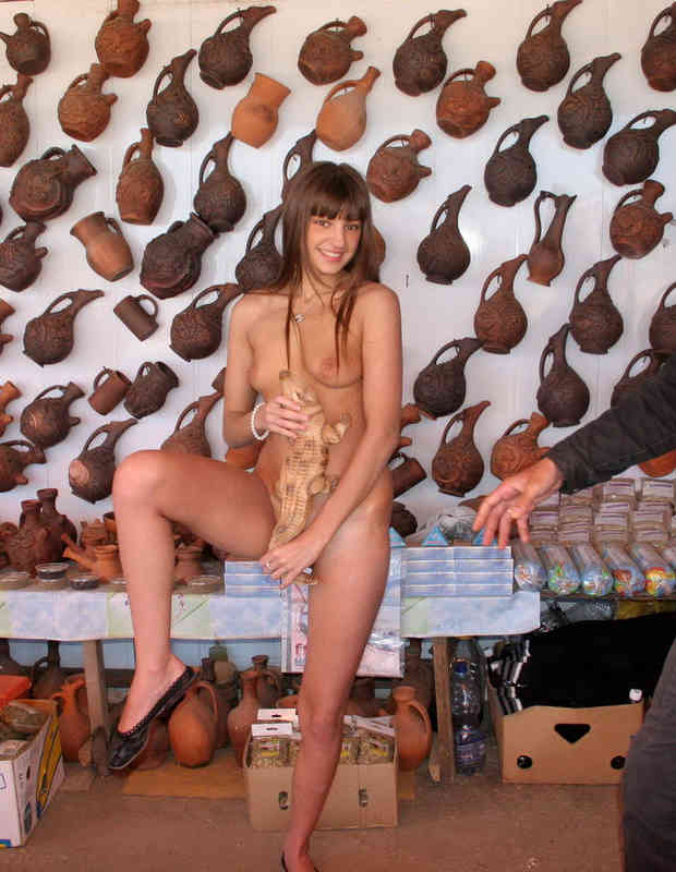 Russian girl undressing in front of the seller in the shop.