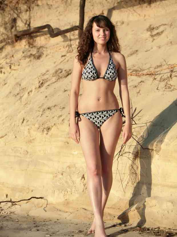 Dazzling redhead strips her bikini on the beach